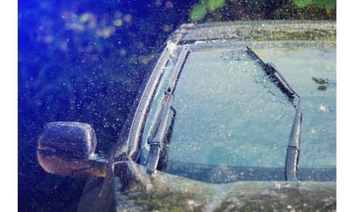 Rain soaked windshield with a wiper going