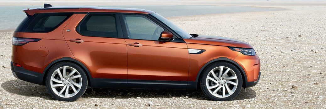 orange 2019 Land Rover Discovery driving on sand
