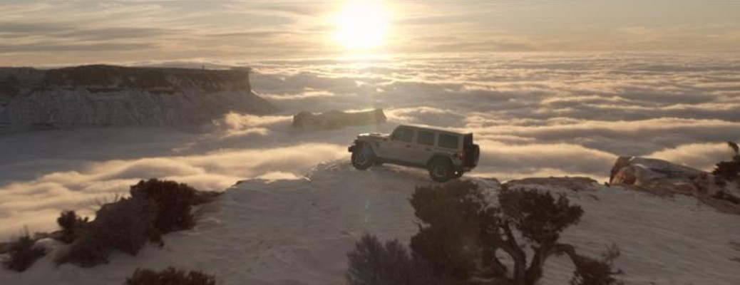 Jeep Wrangler 4xe driving on snowy mountain