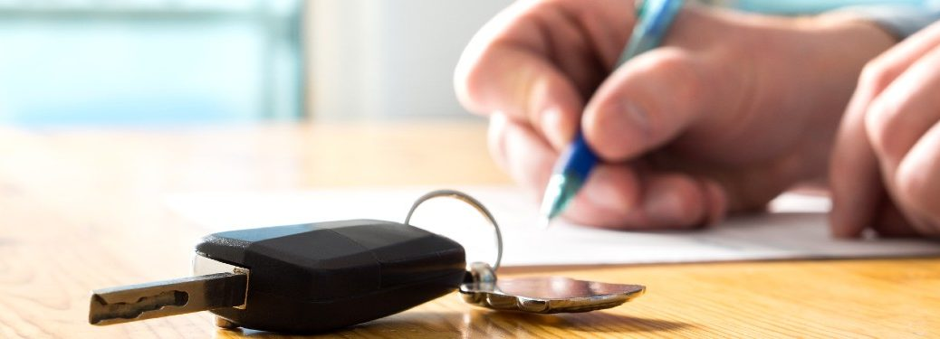 man signing documents for car key fob on table