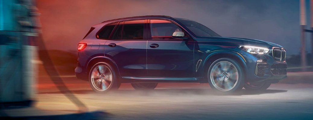 2020 BMW X5 driving by a gas station