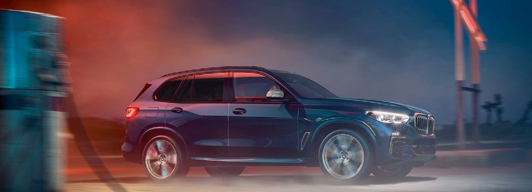 2020 BMW X5 blue exterior passenger side driving at night