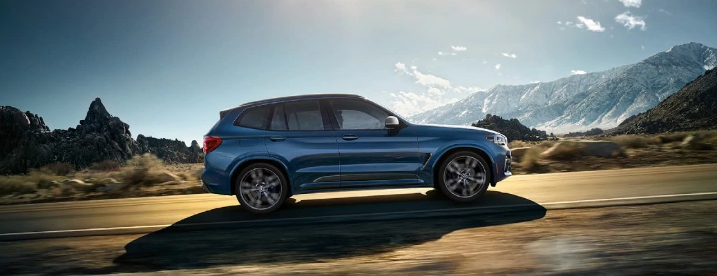 2020 BMW X3 blue driving toward the right at slant vignette
