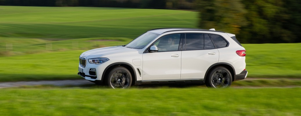 2021 BMW X5 white driving on road through grass with trees in background