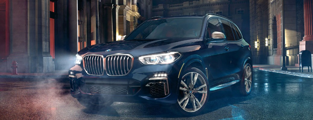 2020 BMW X5 black parked on wet concrete at night in city headlights in