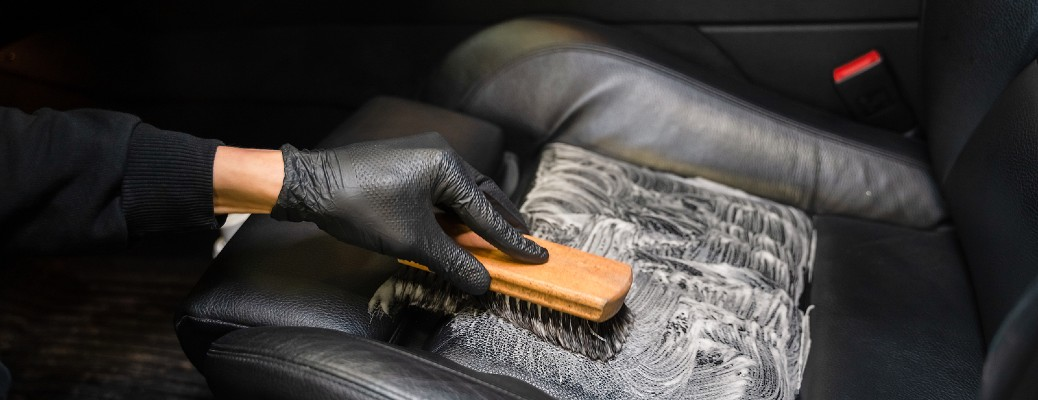 gloved hand brushing leather seat clean