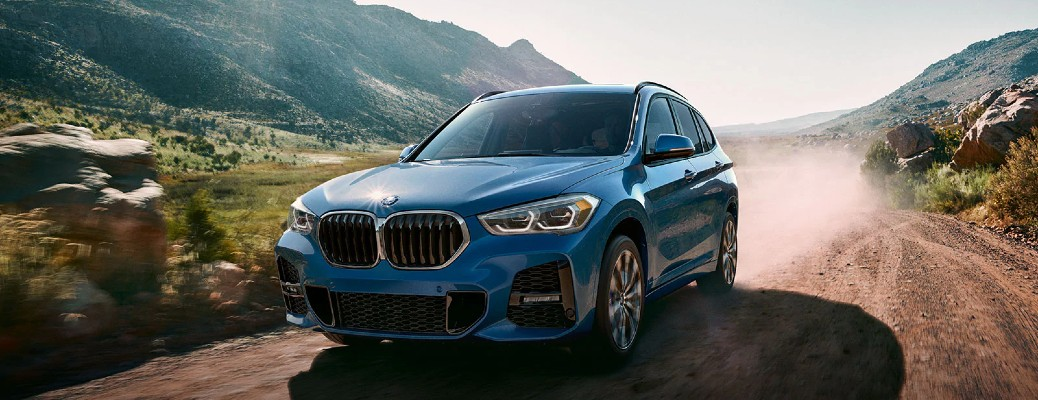 2021 BMW X1 Blue driving down dusty road in mountain valley