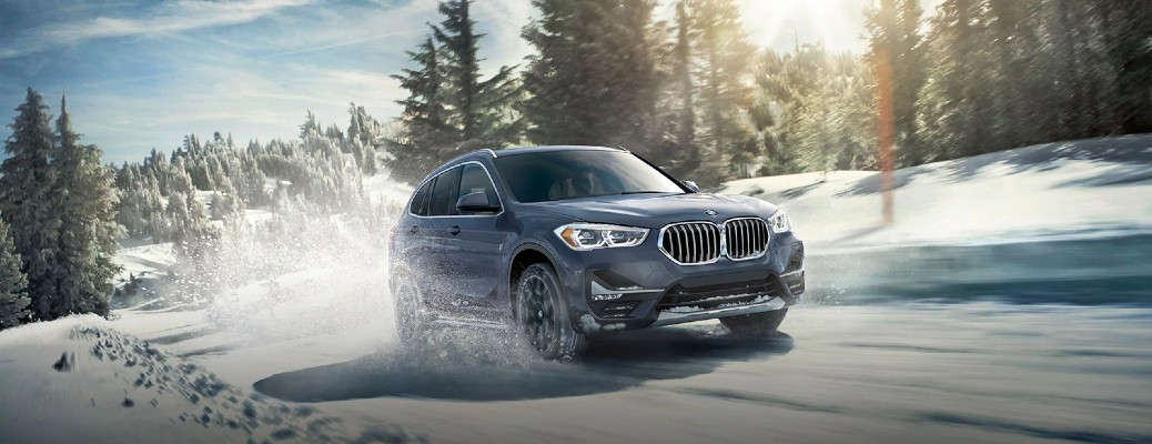 2021 BMW X1 driving on snowy forest road