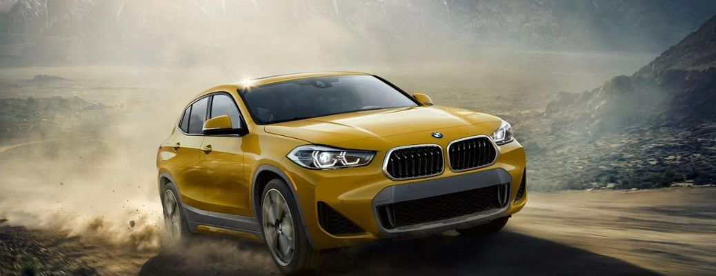 Yellow BMW X2 against the landscape backdrop