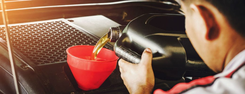 A stock photo of a person pouring new oil into an engine.
