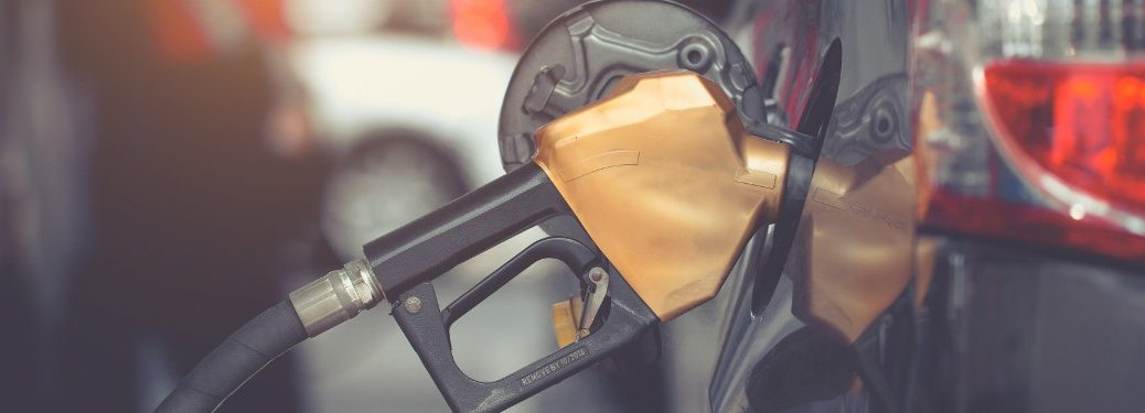 gold fuel pump in SUV at gas station