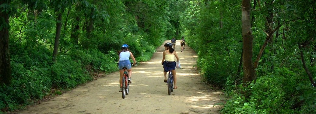 Two people riding their bike on a trail