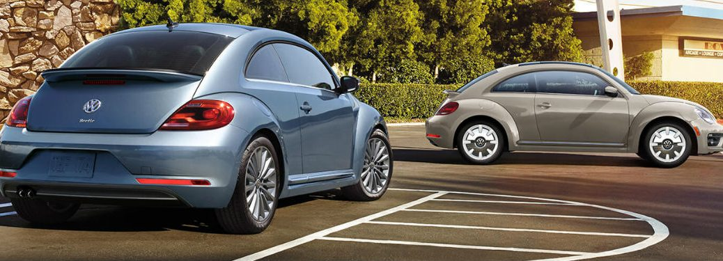 Two Volkswagen Beetle cars parked