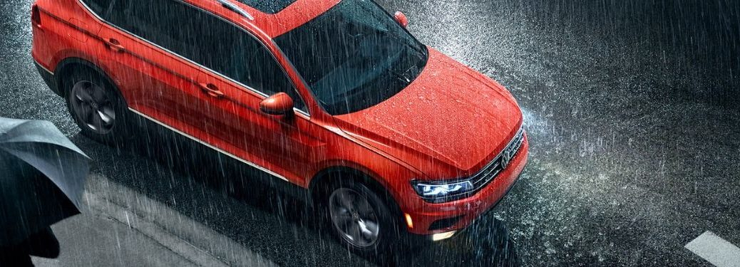 top-down-view-of-orange-Volkswagen-Tiguan-stopped-at-a-crosswalk-in-the-rain