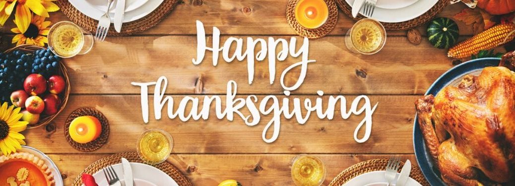 """A wooden table is laid out with a plethora of Thanksgiving dishes. White text in the middle reads, """"Happy Thanksgiving."""""""