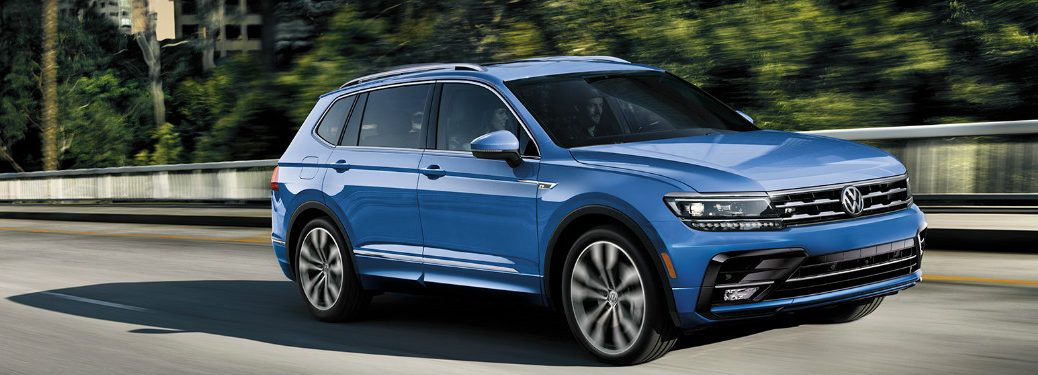 A blue 2020 Volkswagen Tiguan drives along a bright highway under the control of a focused man.