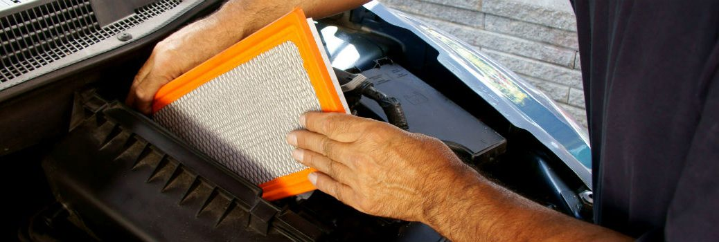 person inserting air filter in a car