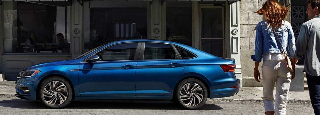 woman-and-man-walking-toward-blue-2019-Volkswagen-Jetta-parked-on-street