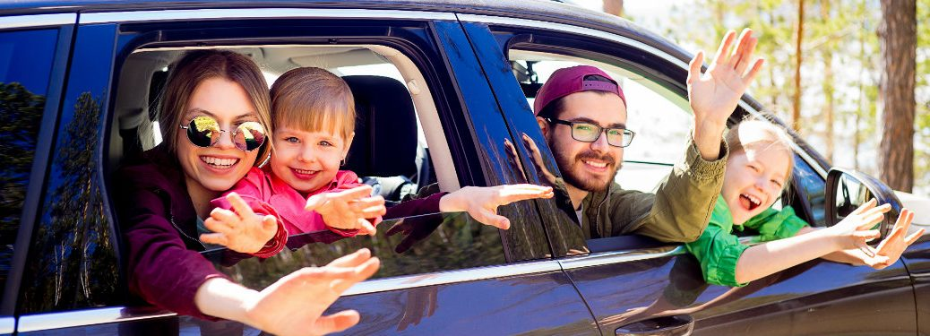 family-waving-out-windows-of-crossover-vehicle
