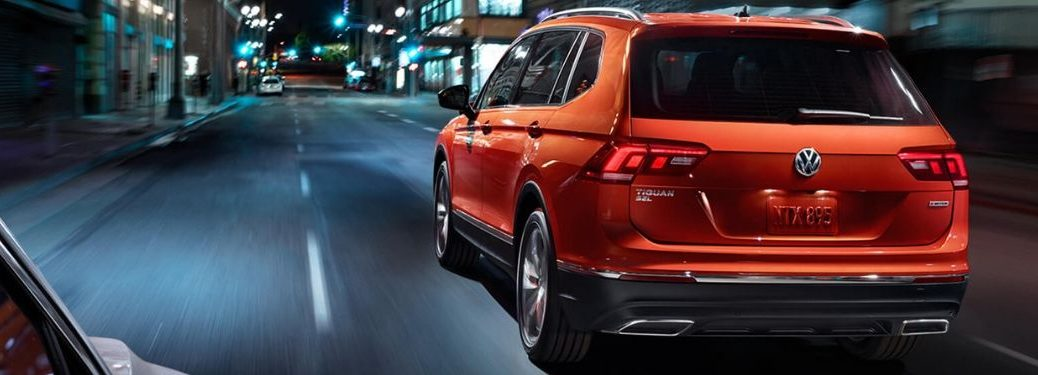 rear-view-of-orange-Volkswagen-Tiguan-driving-down-city-street-at-night