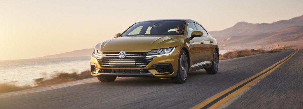 yellow-2019-VW-Arteon-driving-by-the-coast-at-sunset