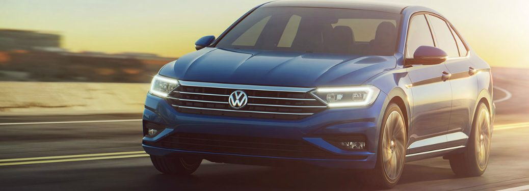 Blue 2019 Volkswagen Jetta cruises around a track as the sun shines upon it.