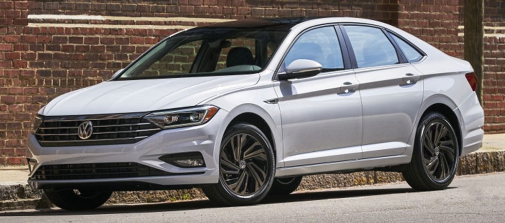 White 2019 Volkswagen Jetta, exterior front/side view, parked in front of a brick building.