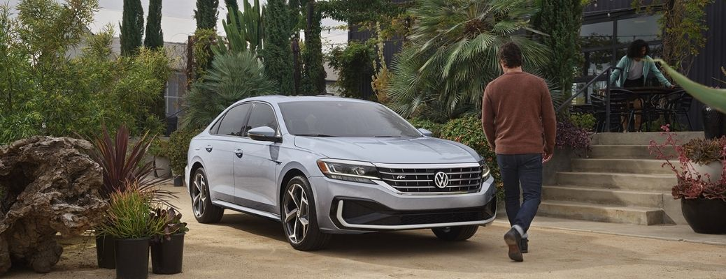 a man walking towards the 2021 VW Passat and a woman arranging the table in the background