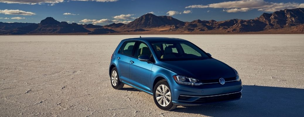 front quarter view of the 2021 VW Golf with mountains in the background and a blue sky with some clouds