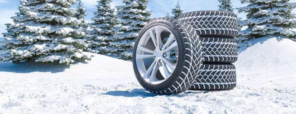 Group of winter tires stacked on snowy backdrop