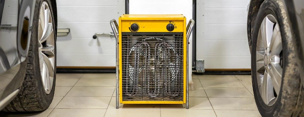 Two vehicles inside garage with space heater running