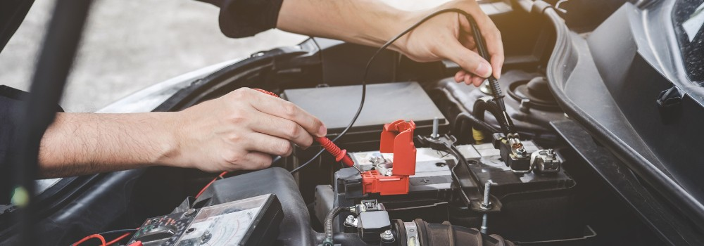 Mechanic using cables to assess battery voltage