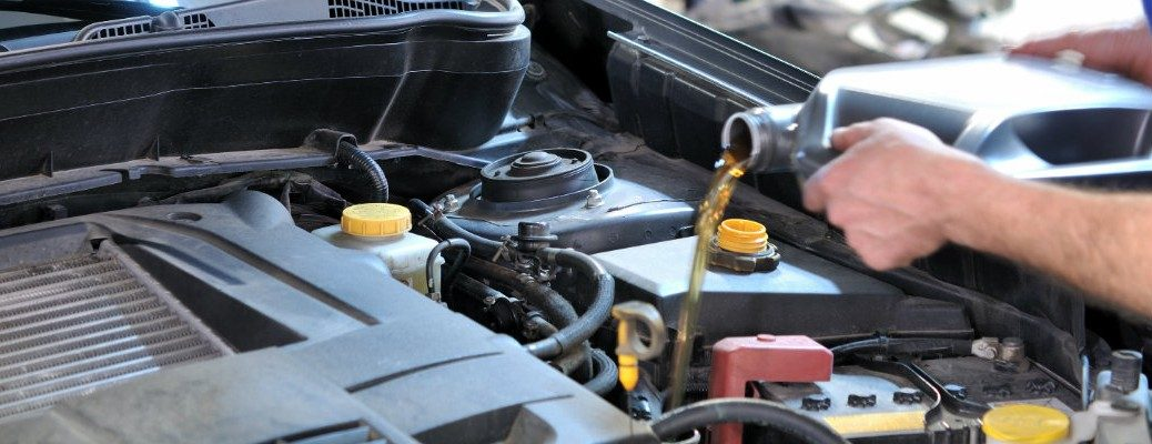 Hands pouring oil into engine bay
