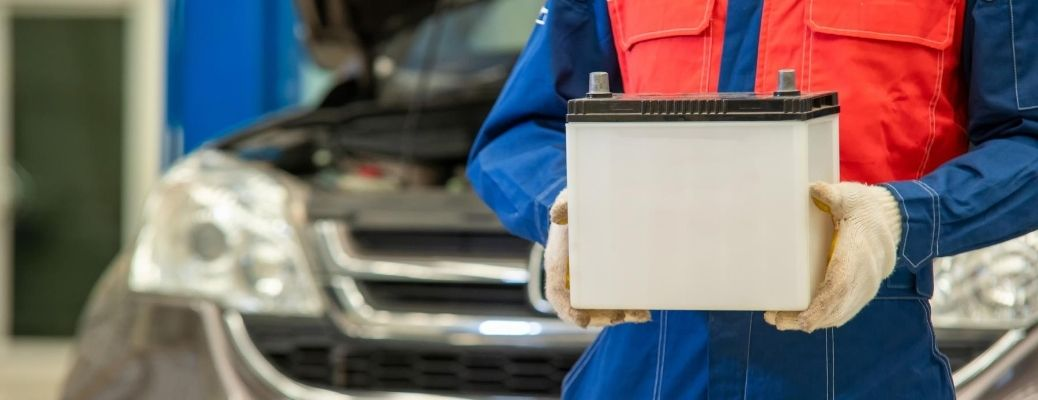 Image of a service technician holding a vehicle's battery