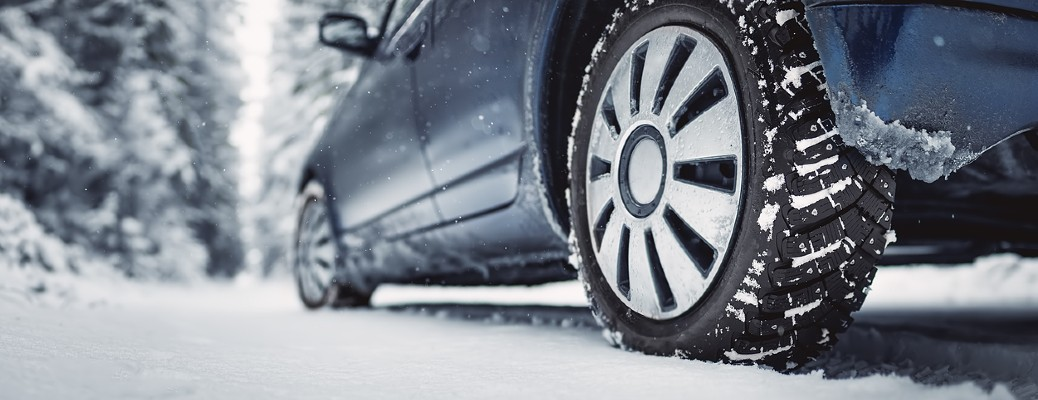 A closeup of the wheels on a blue vehicle driving through snow-covered road