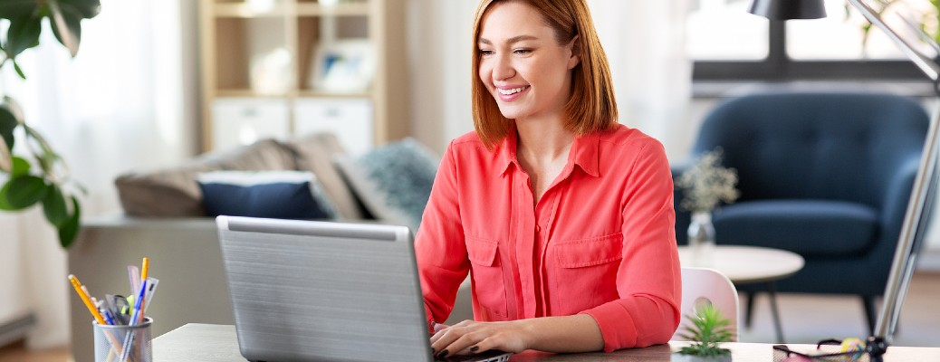 Woman typing on a laptop while smiling