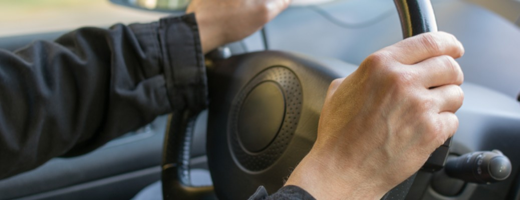 Man with his hands on the steering wheel of a vehicle