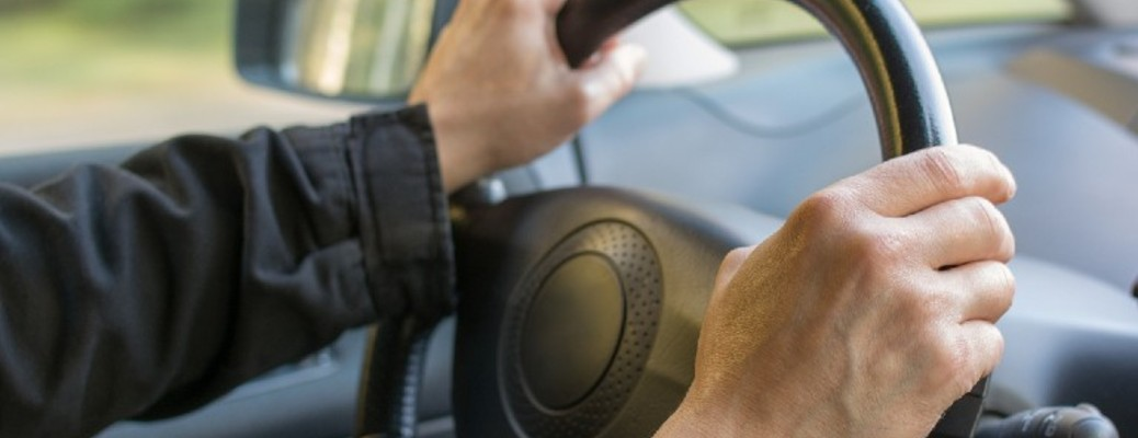 A person with both their hands on a vehicle steering wheel