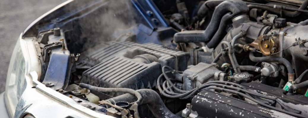 A car overheating with steam coming from under the hood