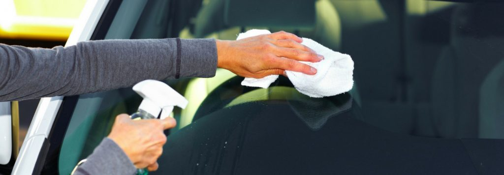 person cleaning windshield with white cloth and spray bottle