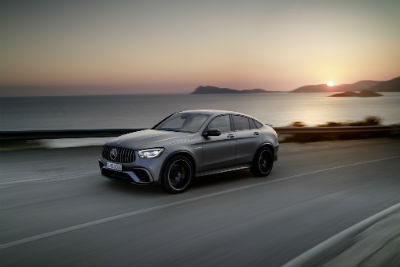 2020 MB GLS Coupe exterior front fascia and driver side on highway with ocean sunrise