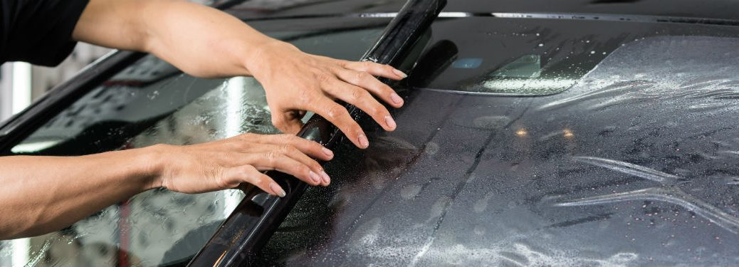 Mechanic tinting windshield in shop
