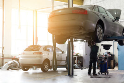car lifted in air in service center with mechanic underneath