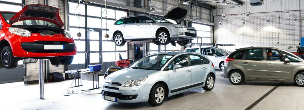 Vehicles in a car repair shop 2 up on lifts