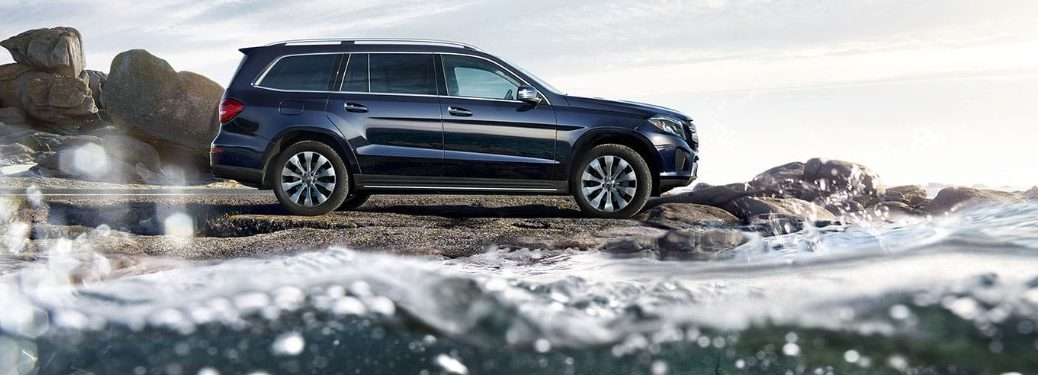 Passenger angle of a blue 2019 Mercedes-Benz GLS parked by the ocean shore
