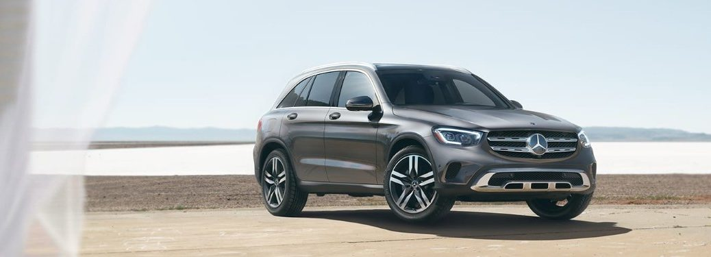 Front passenger angle of a grey 2020 Mercedes-Benz GLC parked on a beach