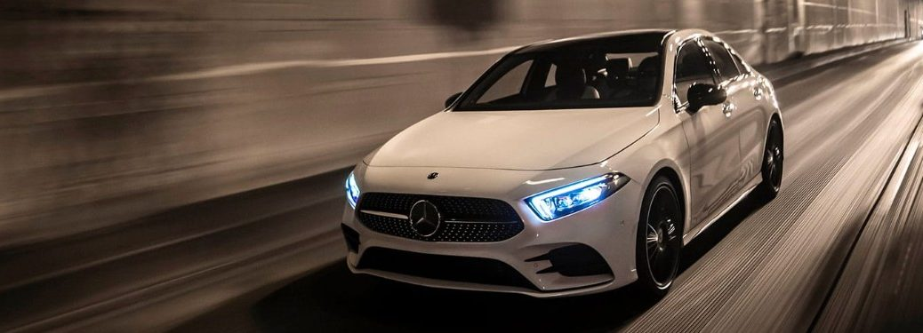 Front driver angle of a white 2019 Mercedes-Benz A-Class driving down a road