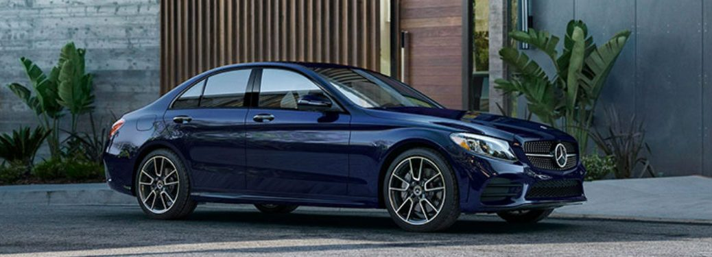 2020 MB C-Class exterior front fascia and passenger side in front of building with plants