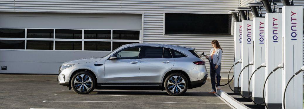 2020 MB EQC exterior driver side with woman behind it at charging station