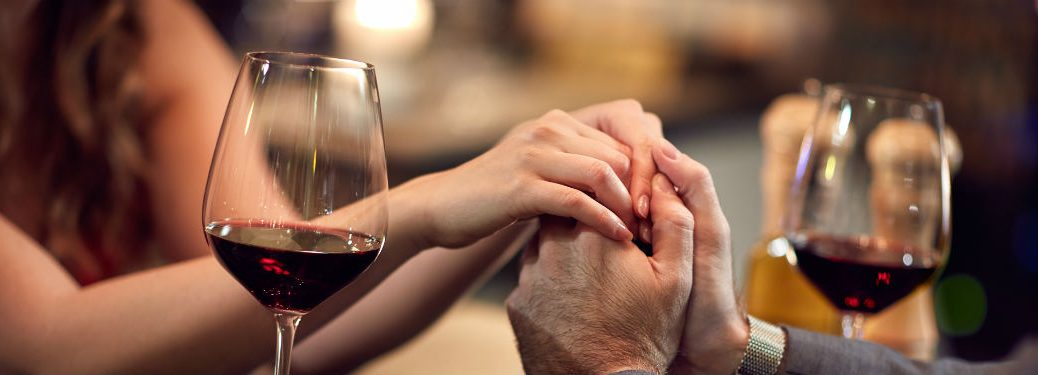 Man holding woman's hands with wine glasses
